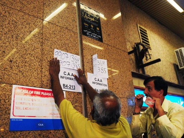 Pakistani airport civil aviation officials put up a sign with a help line number as relatives of victims of a plane crash near Islamabad gather nearby, at the airport in Karachi on April 20, 2012. PHOTO: AFP