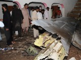 Pakistani villagers look at the debris from a plane following the crash of a Bhoja Air Boeing 737 on the outskirts of Islamabad on April 20, 2012. PHOTO: AFP