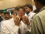 Relative of a passenger on board Bhoja aircraft reacts at Karachi airport. PHOTO:  ATHAR KHAN/ THE EXPRESS TRIBUNE