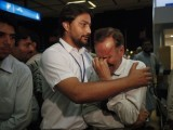 Qamar (R), an uncle of a newly married couple who were victims of the Bhoja Air airliner crash, is consoled by a Civil Aviation Authority official at Jinnah International Airport in Karachi April 20, 2012. PHOTO: REUTERS