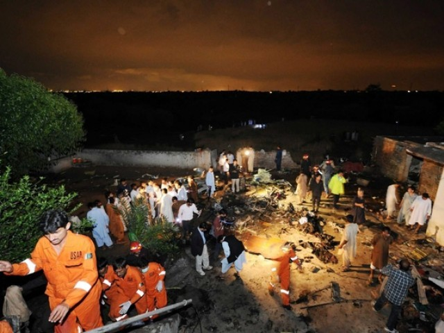 Rescue workers and local residents search the site of a plane crash in Rawalpindi on April 20, 2012. PHOTO: AFP