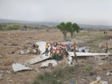 Rescue workers gather near the carnage of Bhoja Air flight B4-213 that crash landed in a wheat field in Koral town late Friday evening.  PHOTO : MYRA IQBAL