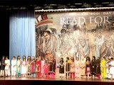 Children singing on stage with a backdrop mural of great Muslim scholars. PHOTO: MYRA IQBAL, APP