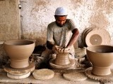 A potter shaping pottery into various styles. PHOTO: ARIF SOOMRO/ EXPRESS