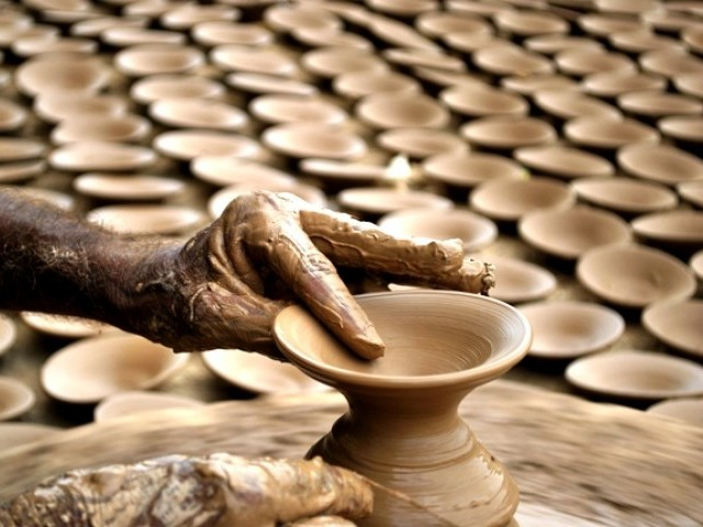 A potter using a potter's wheel to make pots of clay. PHOTO: ARIF SOOMRO/ EXPRESS