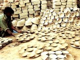 A potter collects sun-dried pottery. PHOTO: ARIF SOOMRO/ EXPRESS