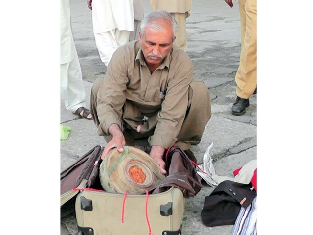 Worker of the bomb disposal squad opens the bag containing explosives. PHOTO: RASHID ALI/EXPRESS