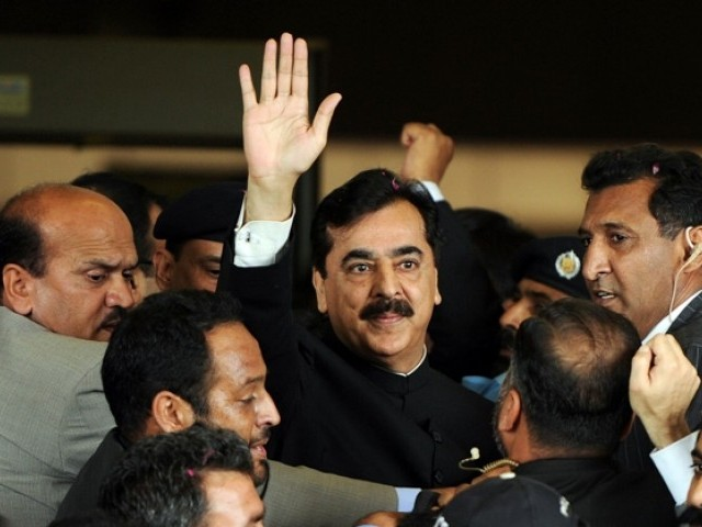 Prime Minister Yousaf Raza Gilani (C) is escorted by security as he waves upon his arrival at the Supreme Court building in Islamabad on April 26, 2012. PHOTO: AFP