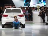 A man man sits behind a Kia 'Forte' car at the Auto China 2012 car show in Beijing on April 26, 2012. PHOTO: AFP