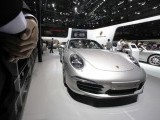 A staff member stands next to a Porsche E911 Carrera S at Auto China 2012 in Beijing, April 24, 2012. PHOTO: REUTERS