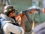A Pakistani police commando fires at alledged criminals during an operation against criminal gangs in the Lyari area in Karachi on April 28, 2012. PHOTO: AFP