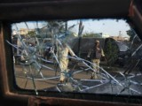 Armed policemen are seen through the shattered window of a police van which was damaged during a firefight with gang members in Karachi's Lyari area April 28, 2012. PHOTO: REUTERS
