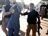 Policemen escort a man following his arrest as security officials conducted an operation to clean up criminals in Lyari. PHOTO: PPI