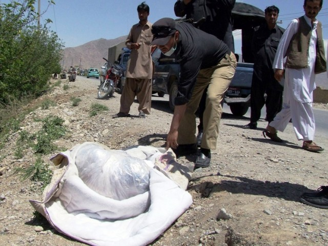 A Pakistani police official looks at the covered dead body of British aid worker Khalil Rasjed Dale (L), found on a road side in Quetta on April 29, 2012. PHOTO: AFP