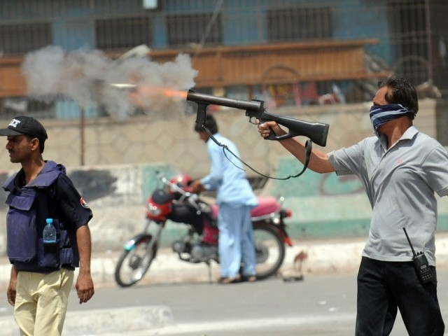A policeman fires teargas toward residents of southern neighbourhood Lyari during a protest against the government and police operation in troubled Lyari area in Karachi on April 30, 2012. PHOTO: AFP