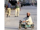 A physically challenged person leaves after filling containers with drinking water during the police operation in Lyari. PHOTO: INP