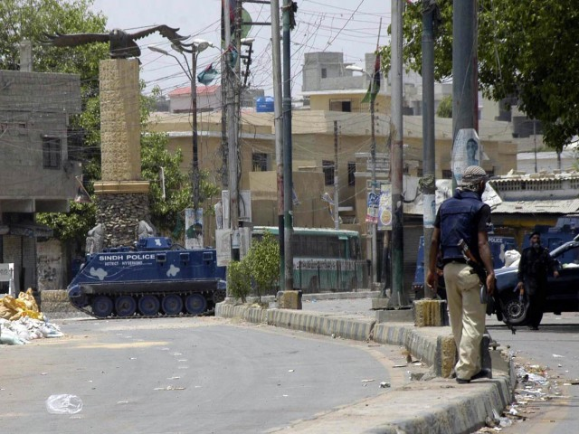 Police armooured personnel carriers stand vigilant in Lyari on Wednesday. PHOTO: RASHID AJMERI/EXPRESS