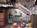 A woman combs her hair in the back courtyard of a traditional colonial-era Board House dating back about a century in the Murray Town neighbourhood of Sierra Leone's capital Freetown April 28, 2012. Board Houses are a reconstruction of cabin-like structures built in the 18th century on the American eastern seaboard. There were some modifications though, notably a three-foot base layer of porous local stone (seen here) that helped anchor the house down during Sierra Leone's torrential wet season. Picture taken April 28, 2012. PHOTO: REUTERS