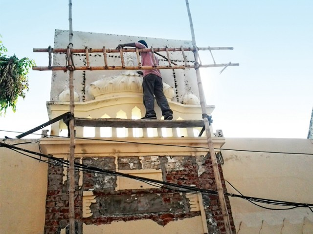 A hoarding is installed behind the chhatri (flattened dome) at the entrance, so that the worship place does not look like a mosque. PHOTO: EXPRESS TRIBUNE