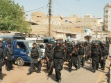 The paramilitary FC personnel entering Lyari as police backup on Friday. PHOTO: ONLINE