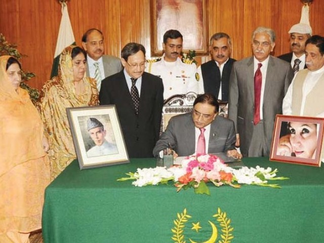 This file photo shows President Zardari signing a bill into law. PHOTO: SANA/FILE