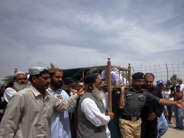 A policeman helps relatives carry the body of Shah Nawaz Khan, who was killed by an unidentified gunman in Quetta May 8, 2012. PHOTO: REUTERS