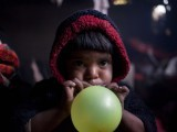 A boy blows balloon to celebrate a doll's wedding. PHOTO: MYRA IQBAL/ THE EXPRESS TRIBUNE