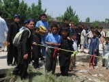 Local residents gather at the crash site of a light Mushshak plane after it crashed on a house in the Rashkai area, 160 kilometres northwest of the capital on May 17, 2012.  PHOTO: MUHAMMED IQBAL/ THE EXPRESS TRIBUNE