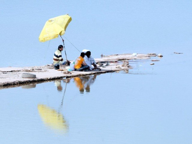 People enjoy at the Rawal Lake as water level begins to recede. PHOTO: QAZI USMAN/ EXPRESS