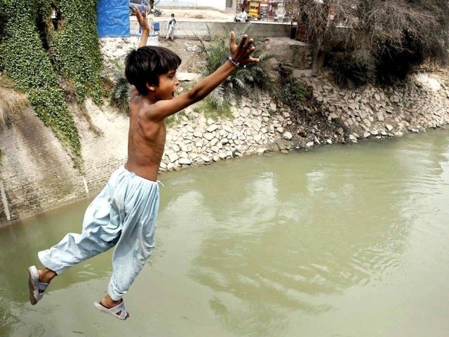 A boy jumps into the Channel Mori Canal in Hyderabad to beat the rising heat.  PHOTO: APP