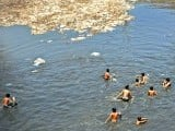 Pakistani youths cool off near floating trash in a polluted canal during a hot day in Rawalpindi May 11, 2012. Heat-wave conditions in Pakistan brought a high of 41 degrees celsius in some parts of the country. PHOTO: AFP