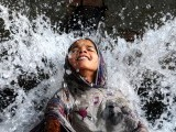 A Pakistani girl cools off in a water channel in Lahore on May 11, 2012. Heatwave conditions in Pakistan have brought temperatures in excess of 40 degrees celsius in many parts of the country. PHOTO: AFP