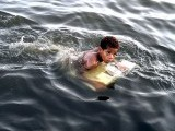A boy uses a board to float, enjoying his dip at Native Jetty in Karachi. PHOTO: INP