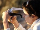 A woman checks her smart phone while watching the first annular eclipse seen in the U.S. since 1994 with special glasses to protect her eyes on May 20, 2012 in Grand Canyon National Park, Arizona.  PHOTO: AFP