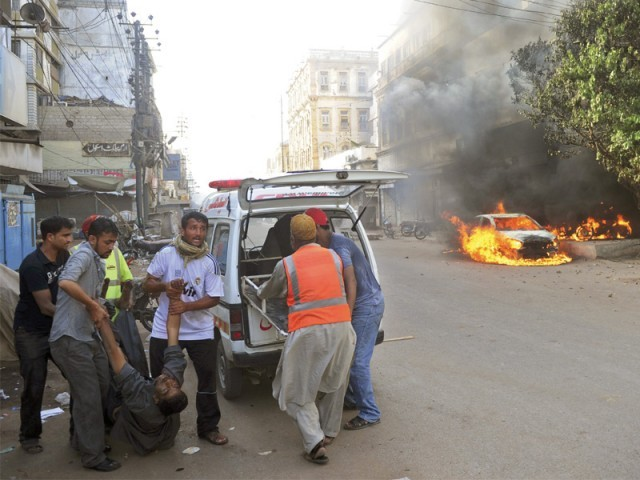 Volunteers take a man injured in the firing on Napier Road to hospital. Gunmen opened fire on a pro-Sindh rally on Tuesday. At least 10 people were killed as violence erupted, police said. Gunmen and arsonists went on a rampage. PHOTO: AFP