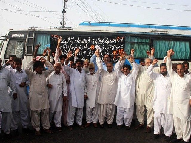 Bus transporters hold a demonstration against the firing incident on a bus near Qazi Ahmed, on MA Jinnah road on Saturday. PHOTO: ONLINE