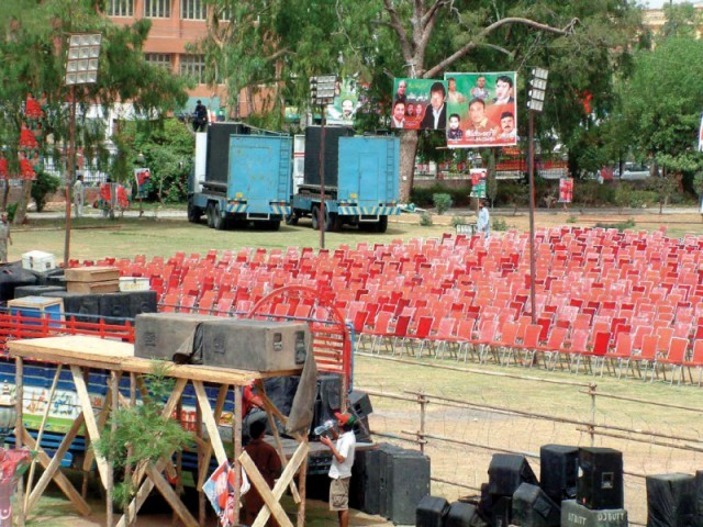 PTI workers prepare the stage for party rally in Liaquat Bagh. PHOTO: NNI
