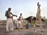 Muhammad Hanif, 16, shows off his cartwheel to his family members. Hanif, who has polio, works as a day laborer. PHOTO: MYRA IQBAL/ THE EXPRESS TRIBUNE