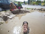 Eleven-year-old Miramzaadi swims in a mud hole on a hot summer's day near a traffic signal where she and other young afghan children wash car windows for a living. PHOTO: MYRA IQBAL/ THE EXPRESS TRIBUNE