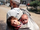A man carries his children in a cloth bag in Nowshera district. PHOTO: ONLINE