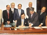 Prime Minister Yousaf Raza Gilani signs the approval for the 5th budget, a first for a democratically elected government in Pakistan. PHOTO: APP