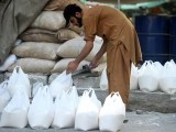 A Pakistani worker prepares bags of wheat flour outside a shop in Islamabad on June 1, 2012. Pakistan's economy grew by 3.7% in the current fiscal year with inflation up by 10.8%. PHOTO: AFP