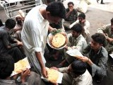 A Pakistani waiter distributes free bread to impoverished men in Karachi on June 1, 2012. Pakistan's economy grew by 3.7% in the current fiscal year, with unemployment soaring. PHOTO: AFP