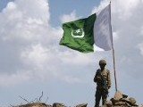 a-pakistani-soldier-poses-for-a-photo-under-pakistans-national-flag-planted-atop-the-baine-baba-ziarat-mountain-in-swat-district-2-2-2-2