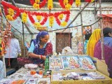 Heera Maasi, 60, arranges Diwali festival souvenirs as she awaits customers along a roadside stall in Karachi October 26, 2011. Prayers and offerings are made to Hindu deities on the occasion of Diwali, the annual festival of lights. PHOTO: FILE