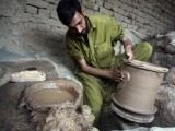 A potter decorating clay pots. PHOTO: MUHAMMAD IQBAL/ THE EXPRESS TRIBUNE