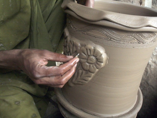 Potter decorating a clay pot. PHOTO: MUHAMMAD IQBAL/ THE EXPRESS TRIBUNE