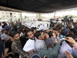 Thousands of mourners accompany Mehdi Hassan's body to a graveyard. PHOTO: INP