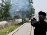 A policeman fires tear gas on protesters in Faisalabad. PHOTO: INP