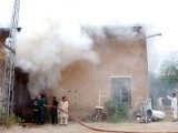 Fire brigade officials trying to extinguish the IESCO office in Attock after protesters set it on fire. PHOTO: INP
